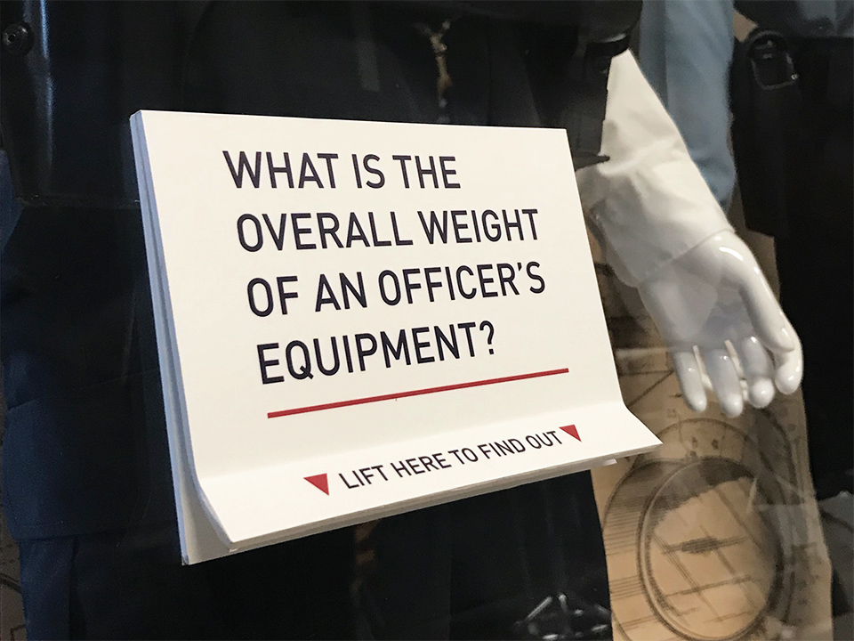 A flip-up card on the CPD Uniforms and Equipment display acts as an interactive exhibit component