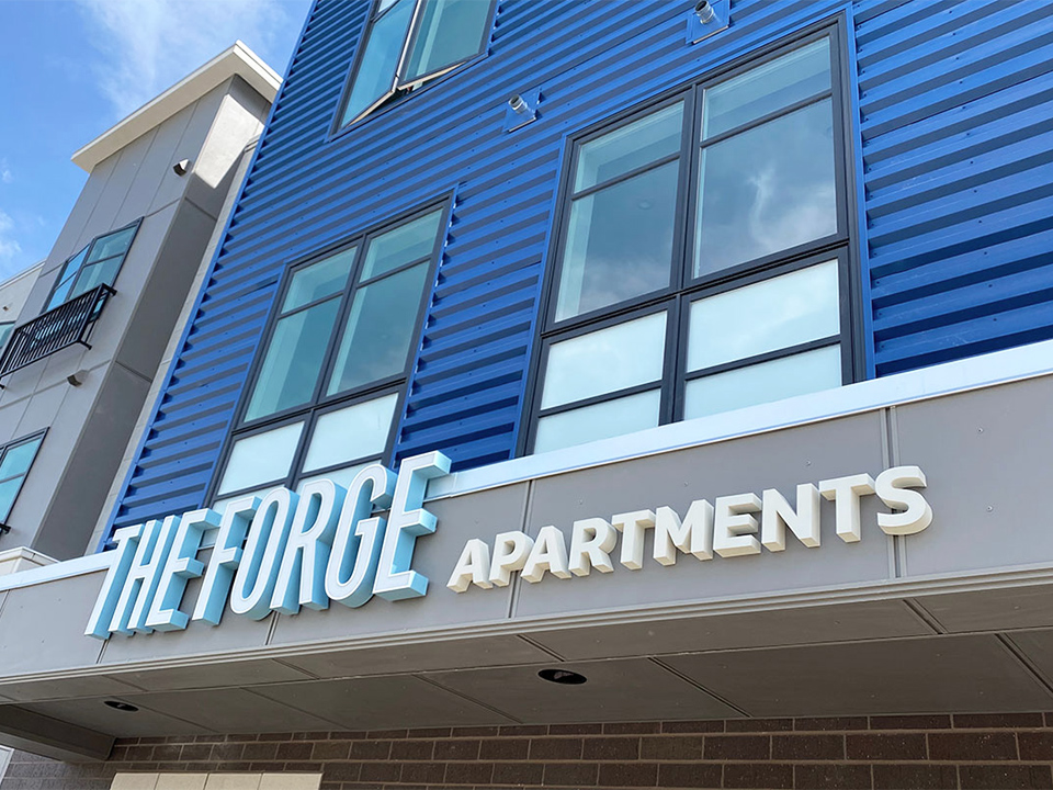 Large-scale exterior signage at The Forge Apartments stays true to the brand aesthetic, making a statement that identifies the building