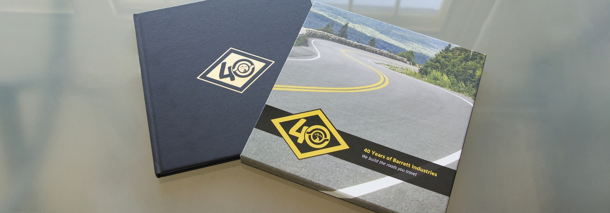 The Barrett Industries book is contained in a custom designed sleeve. When removed from the sleeve, you can see the custom gold foil logo commemorating their 40th anniversary.